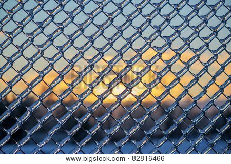 Sunset Behind An Ice Covered Chain Link Fence