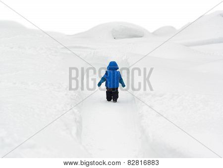 Boy Walking Through Snowy Path