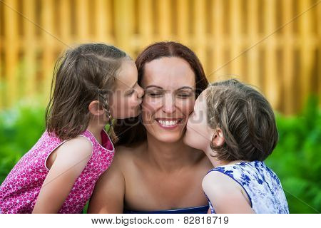 Daughters Kissing Their Mother