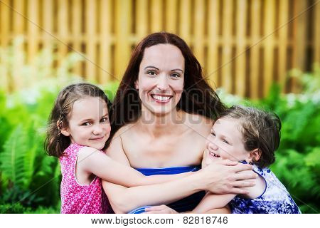 Daughters Hugging Their Mother