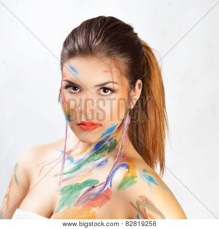 Woman face painted. Beautiful fashion color girl face art close up portrait.