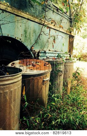 Old rusted bus with trash cans