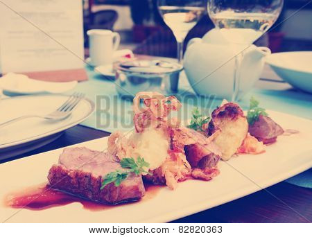 Medium rare fried duck breast with fried onion and sauerkraut, modern czech cuisine, toned image