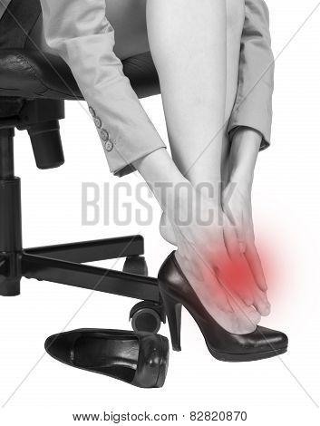 Businesswoman massaging her aching foot