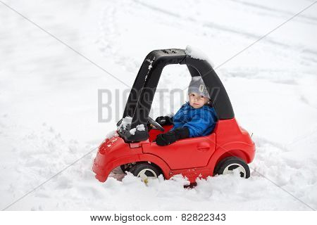 Young Boy Sitting In A Toy Car Stuck In The Snow