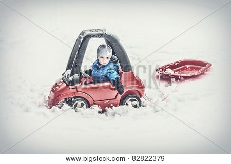 Young Boy Sitting In A Toy Car Pulling A Sled