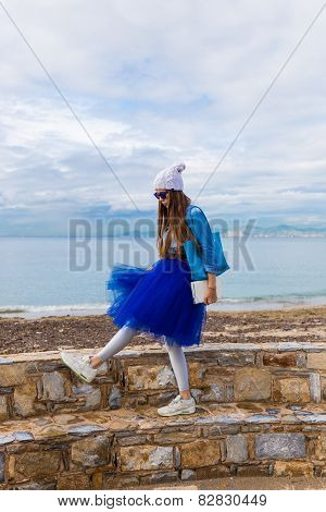 Pretty young girl in blue pettiskirt  with book ang bag