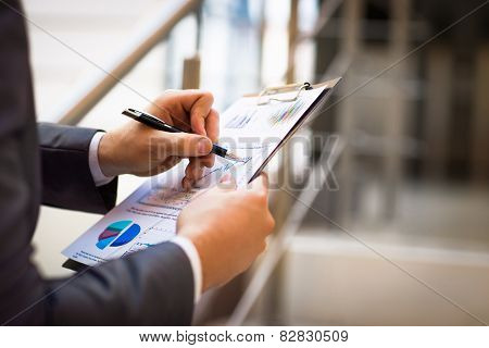 female and male hands pointing at business document while discussing it
