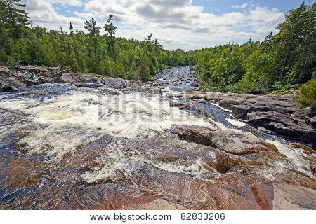 Looking Down A Rushing River On A Sunny Day