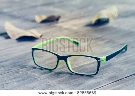 Sight glasses and dried leafs on bamboo floor in vintage
