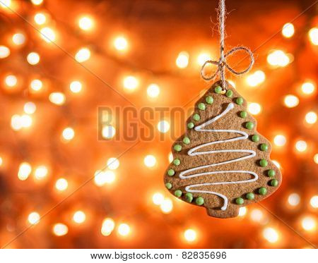 Gingerbread cookie hanging over bokeh lights background in a christmas theme