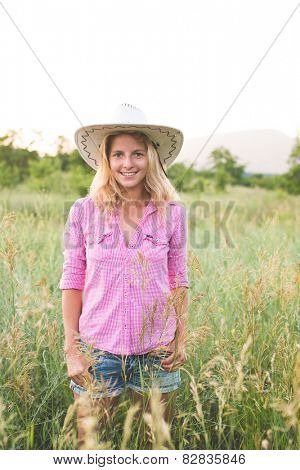 blonde cowgirl posing countryside