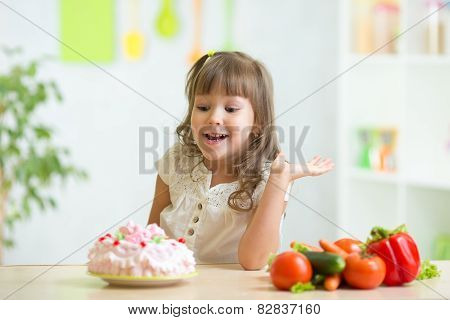 kid choosing between healthy vegetables and tasty cake