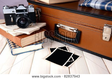 Vintage suitcase with clothes and books on table on dark background