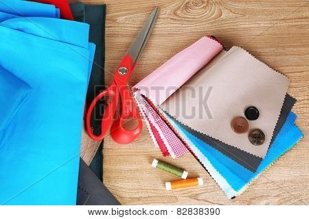 Colorful fabric samples with buttons, scissors and threads on wooden table background