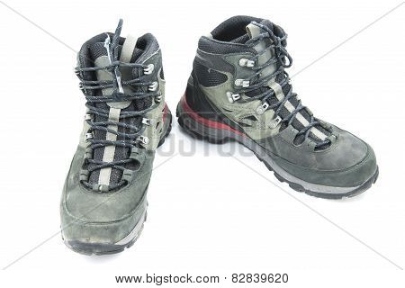 Pair of dirty grey hiking boots isolated on white background.