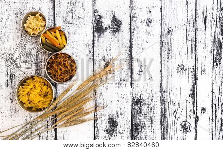 different kinds ofdifferent kinds of pasta on textured wooden table