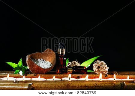 Beautiful composition with aromatic oils and candles on table on dark background
