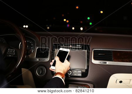 Man using smart phones while driving at night, close-up