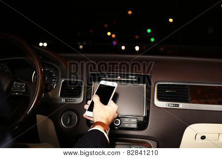 Man using smart phones while driving at night, close-up