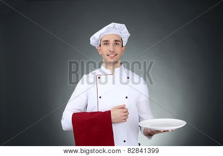 Chef with towel on hand and plate on dark background