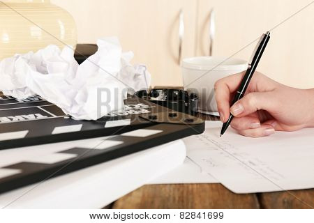 Female hand with pen at desktop with moving clapper and working mess on light cupboard background