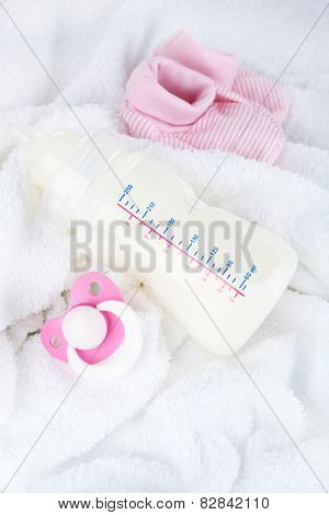Baby milk bottle, pacifier and babys bootees on towel