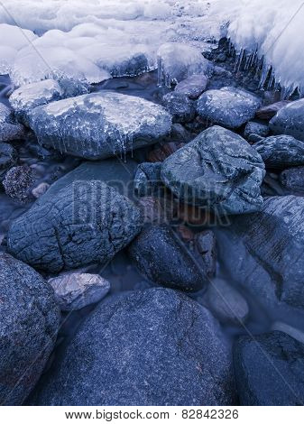 Ice-covered stones in the water. Lake Teletskoye, Altai Republic, Russia