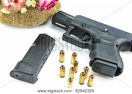 handgun pistol and flower on white background.