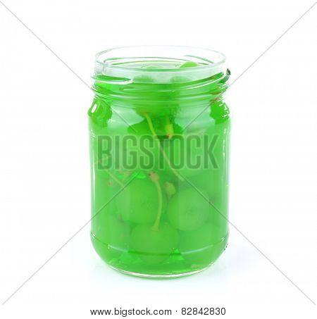 Homemade jar of green maraschino cherry isolated on white background