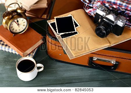 Vintage suitcase with books and camera on wooden background