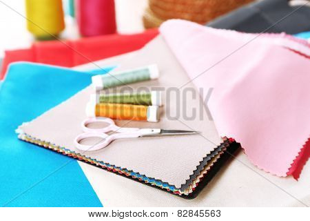 Colorful fabric samples, threads and scissors on wooden table background