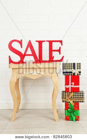 Sale with bags and gifts on side table in room