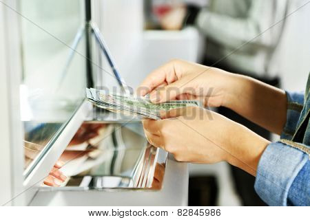 Female hand with money in cash department window. Currency exchange concept