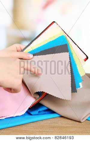Colorful fabric samples in female hands on bright blurred background