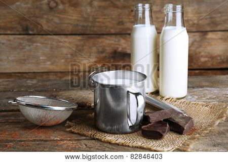 Metal mug and glass bottles of milk with chocolate chunks and strainer of cocoa on burlap cloth and rustic wooden planks background