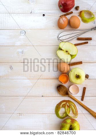 food ingredients for the preparation apple pie on a white wooden background