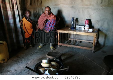 Internal View Of Maasai Hut, Black Woman And Children  Indoors.