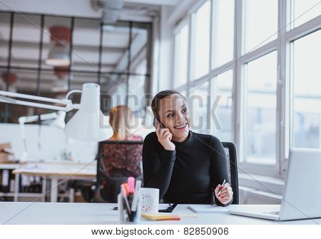 Woman Using Mobile Phone While At Work