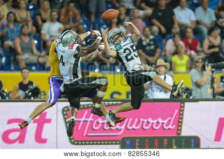ST. POELTEN, AUSTRIA - JULY 27 DB Andreas Bertsch (#25 Raiders), DB Talib Wise (#4 Raiders) and WR Stefan Holzinger (#17 Vikings) fight for the ball at Austrian Bowl XXVII.