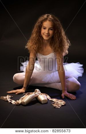 Smiling ballet student sitting on floor cross-legged, smiling, looking at camera, shoes front of her.