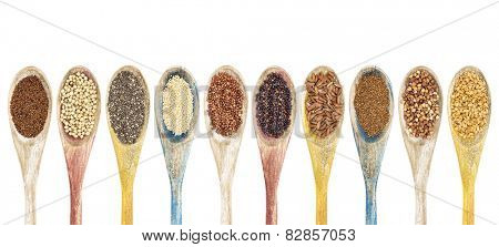 a collection of gluten free grains and seeds on isolated wooden spoons - kaniwa, sorghum, chia, amaranth,red quinoa, black quinoa, brown rice, teff, buckwheat, gold flax (from left to right)