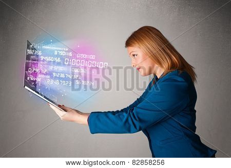 Attractive casual woman holding laptop with exploding data and numers