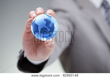 Business man holding a blue globe in his hand symbol for global business, communications or environmental conservation