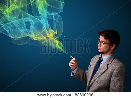 Handsome young man smoking cigarette with colorful smoke