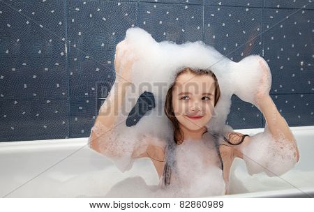 Little Girl Sitting In A Bath And Imposes Soap Suds On Her Head