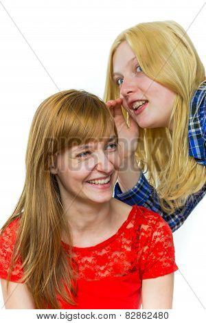 Blonde girl whispering in ear of redhead girl
