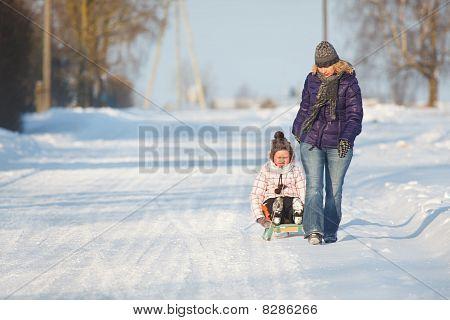 Mother Pulling Daughter On Slegde