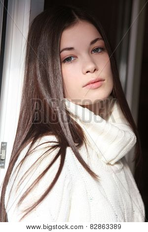 Casual portrait of young beautiful girl in white pullover