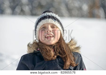 A Smiling Girl With A Cap In The Snow